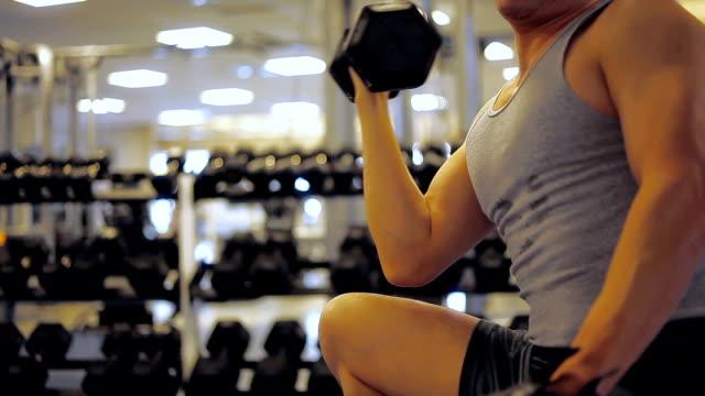 vidéos et rushes de man doing muscle strength exercise workout at gym - seulement des jeunes hommes