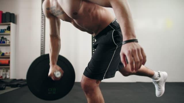 mann macht einen arm langhantel reihe, während auf einem bein stehen - bizeps stock-videos und b-roll-filmmaterial