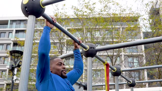 a man doing pull ups at an outside gym in the city - one young man only stock videos & royalty-free footage