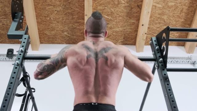 vídeos y material grabado en eventos de stock de hombre haciendo pull ups en el gimnasio funcional - un solo hombre de mediana edad