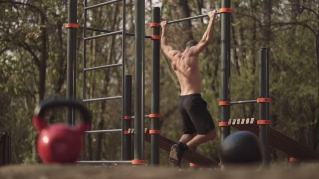 vídeos de stock e filmes b-roll de man doing pull ups - flexão de braço