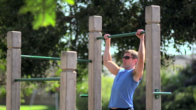 a man doing pull-ups at a park. - slow motion - pull ups stock videos & royalty-free footage