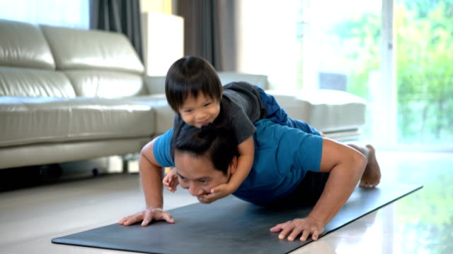 man doing push ups with happy baby on his back at home. - sollevare video stock e b–roll