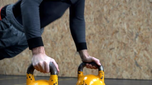 vídeos y material grabado en eventos de stock de hombre haciendo flexiones con la campana de la tetera en el entrenamiento de la aptitud de la cruz-trabajando en un gimnasio - entrenamiento sin material