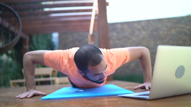 man doing push-ups during a virtual exercise class at home - dedication stock videos & royalty-free footage