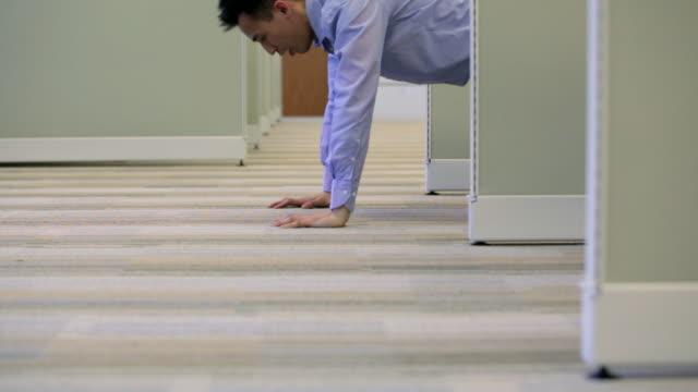 vídeos de stock e filmes b-roll de ms man doing push-ups in office cubicle / vancouver, british columbia, canada - flexão de braço