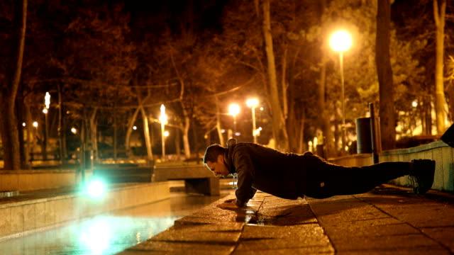 mann tut liegestütze im park in der kalten nacht - dehnen stock-videos und b-roll-filmmaterial