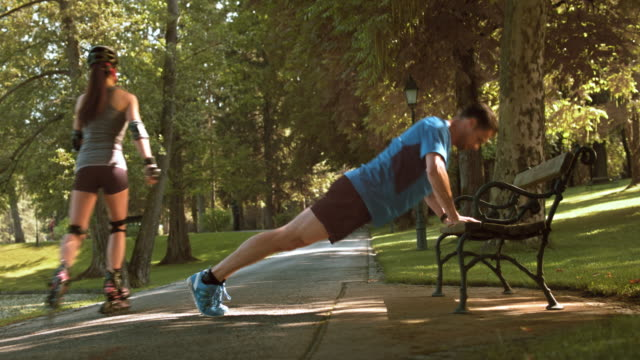 DS Man doing pushups on a bench in the park