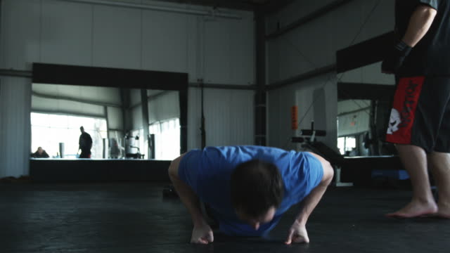man doing pushups while his trainer motivates him