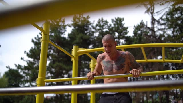 vídeos y material grabado en eventos de stock de hombre haciendo pull ups rusos en bares en el parque - entrenamiento sin material