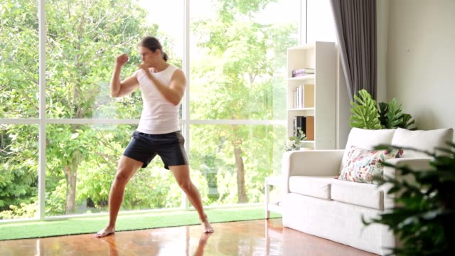 man doing shadow boxing at home. quick jabs. - box container video stock e b–roll