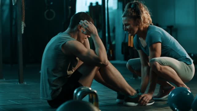 man doing situps and woman holding his legs - cura della persona video stock e b–roll