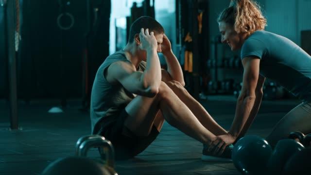 uomo che fa situps e donna che tiene le gambe - cura della persona video stock e b–roll
