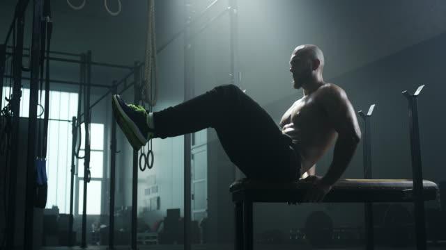Mann Sit auf Bank und seine Bauchmuskeln trainieren