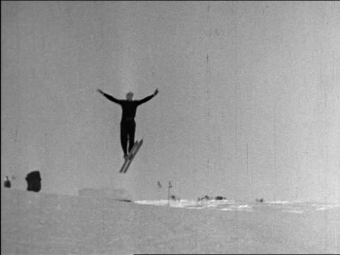 b/w 1940 man doing ski jump over hill with no poles / industrial - ski jumping stock videos and b-roll footage