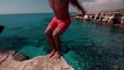 Man doing somersault jumping off cliff and diving into sea