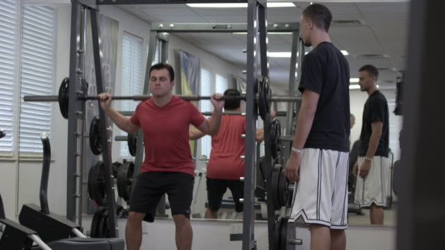 Man doing squat lifts while friend watches.