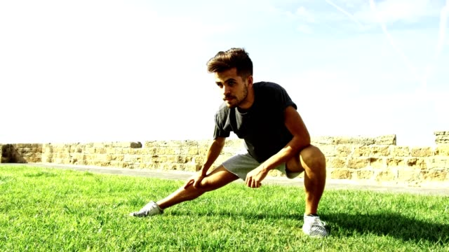 man doing stretching outdoor in the park - stretching stock videos & royalty-free footage