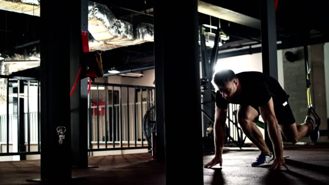 vídeos de stock e filmes b-roll de man doing suspension training in the gym - sports training
