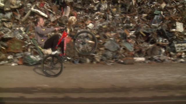 TS PAN man doing wheelie on bike next to scrap metal yard, Gent, Belgium