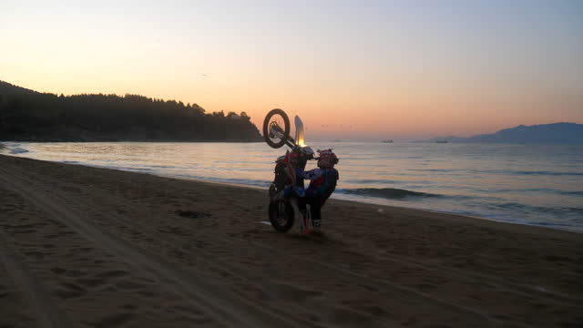 man doing wheelie trick and crashing on motocross motorcycles on the beach at sunset night. - crash helmet stock videos & royalty-free footage