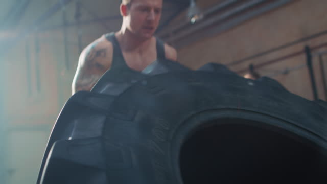 Man doing workout with big tire