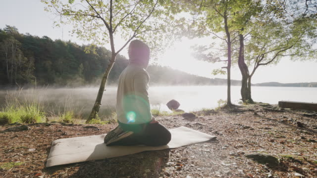 a man doing yoga exercised by a lake in the morning - mindfulness stock videos & royalty-free footage