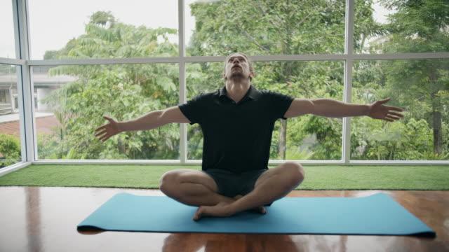 vídeos de stock, filmes e b-roll de homem que faz exercícios da ioga em casa - yoga