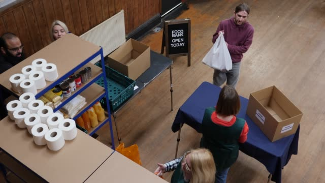 vidéos et rushes de 4k antenne: man don sac plein d'épicerie / nourriture pour une banque alimentaire - pauvreté