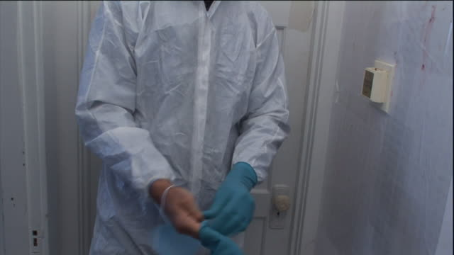 stockvideo's en b-roll-footage met a man dons blue latex gloves and a surgical mask. - protective workwear
