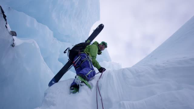 vídeos y material grabado en eventos de stock de man down climbing glacial ice with rope - artículo de montañismo