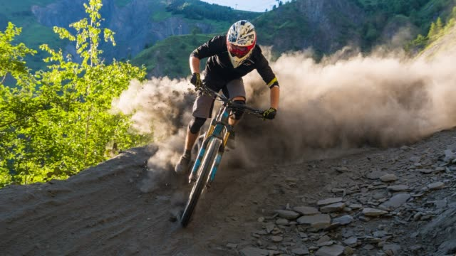 man downhill mountain biking going into a sharp bend on dusty dirt track - andare in mountain bike video stock e b–roll