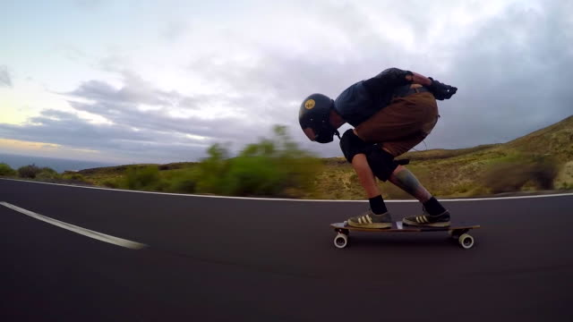 A man downhill skateboarding on a mountain road. - Time-Lapse
