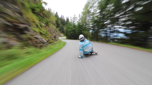 A man downhill skateboarding on a mountain road.