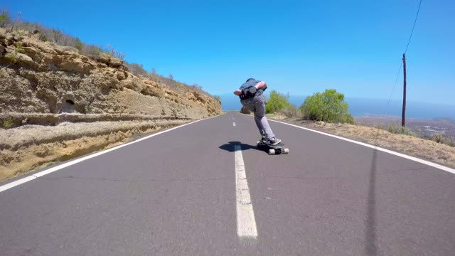 a man downhill skateboarding on a mountain road. - moving down stock videos & royalty-free footage