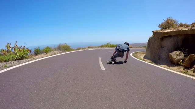 a man downhill skateboarding on a mountain road. - skateboard stock videos and b-roll footage