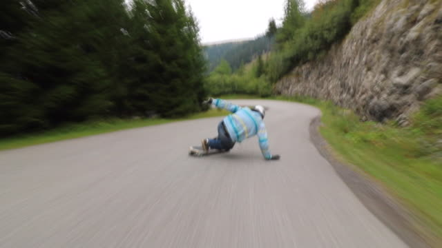 stockvideo's en b-roll-footage met a man downhill skateboarding on a mountain road. - vrijheid