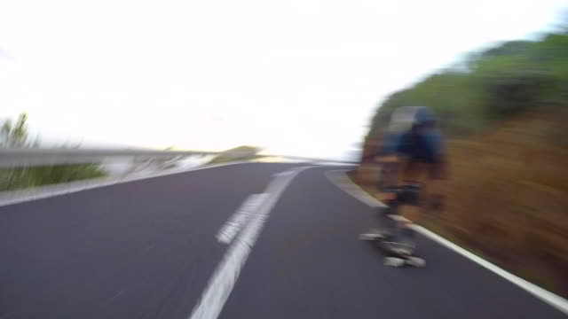 a man downhill skateboarding on a mountain road. - elbow pad stock videos & royalty-free footage