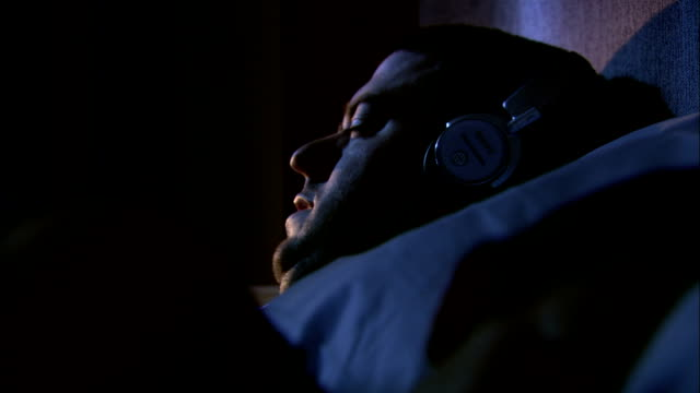 a man dozes in bed while wearing headphones. - headphones stock videos & royalty-free footage