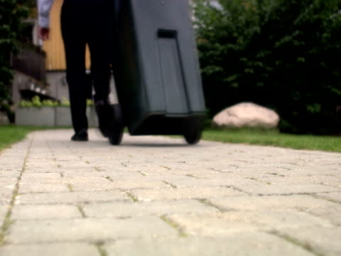 A man dragging a dustbin to a house Sweden.