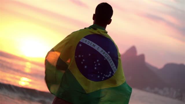 vídeos de stock e filmes b-roll de man draped in brazilian flag watches sunset on ipanema beach - campeonato desportivo