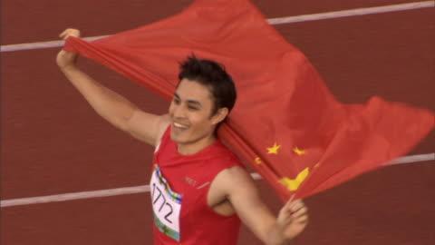 ha ms man draping himself in chinese flag and waving to crowd after winning track event/ sheffield, england - vinna bildbanksvideor och videomaterial från bakom kulisserna