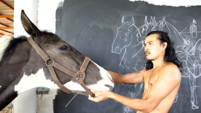 man drawing, designing a horse on the black wall