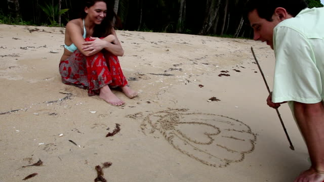Man drawing picture in sand while woman watches on tropical beach.