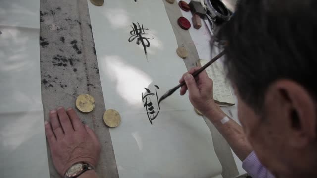 a man draws calligraphy in a roadside stall in xian, china. - chinese script stock videos & royalty-free footage