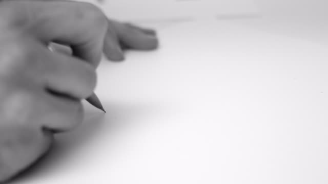 A man draws with a mechanical pencil on a white board.