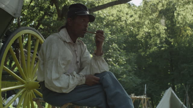 vidéos et rushes de a man dressed as a civil war soldier sits beside a covered wagon and smokes a pipe. - voiture hippomobile