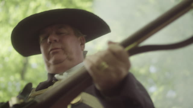a man dressed as a revolutionary war soldier prepares his musket to fire by ripping the top off a paper cartridge and pouring powder into the frizzen and then the barrel. - cartridge stock videos & royalty-free footage
