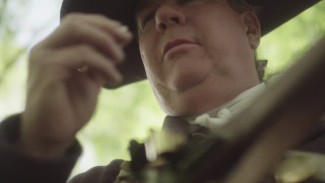 a man dressed as a revolutionary war soldier tears open a paper powder cartridge with his teeth and then pours the powder into the frizzen of a musket. - cartridge stock videos & royalty-free footage