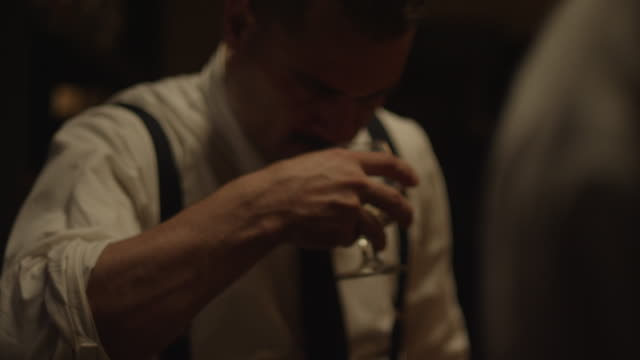 a man dressed as a waiter with an apron sniffs and then takes a drink from a brandy snifter. - brandy snifter stock videos & royalty-free footage